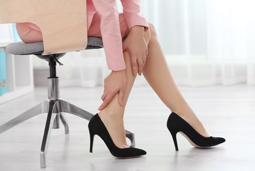Langes Sitzen stresst die Füße Woman suffering from leg pain in office
