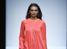 XL-Creolen und eine goldfarbene Kette im Grafikdesign komplettieren das extravagante, asymmetrische Oversized-Dress auf dem Catwalk der Fashion Week