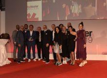 Skechers Deutschland Geschäftsführer Christoph Wilkens mit dem Schuhkurier Award, nebst Laudator Peter Bödeker (5.v.l.), umrahmt vom anwesenden Skechers Team