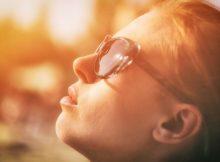 Frau sieht in die Sonne